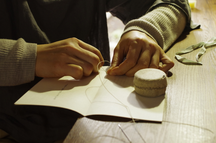 針と糸で本を綴じていく